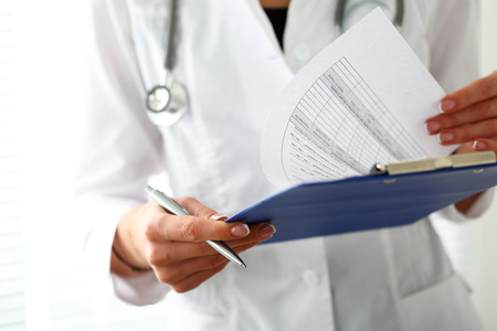 Female medicine doctor hand holding silver pen looking in clipboard pad closeup. Ward round, patient visit check, 911, medical calculation and statistics concept. Physician ready to examine patient Stock Photo