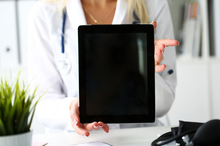 information equipment: Female doctor holding digital tablet pc and showing screen to patient. Diagnostics tools and equipment, therapeutist consultation, information search, document demonstration, prescription concept Stock Photo