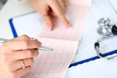 systole: Doctor hands with cardiogram chart on clipboard pad fill medical history with silver pen. Cardio therapeutist assistance, physician make cardiac physical, pulse measure doent, arrhythmia idea
