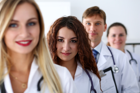 Group of medics proudly posing in row and looking in camera smiling. High level service, best treatment, 911, professional, healthy lifestyle, therapeutist consultation, physical, emergency concept photo
