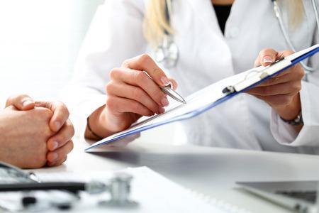 여성 의사 손을 잡고 은색 펜 클립 보드 패드에서 환자 기록 목록 작성. 신체 검사, 검사, 질병 예방, 구청 방문, 수표 검사, 911, 처방 처방, 건강한 생활