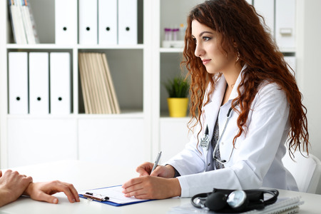 prescription pad: Beautiful smiling female doctor hold silver pen filling patient history list at clipboard pad. Physical, exam, er, disease prevention, ward round, 911, prescribe remedy, healthy lifestyle concept