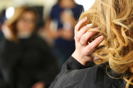 shorten: Blonde woman at hairdresser checking and fixing her new curly hairdo with hand. Keratin restoration, latest trend, fresh idea, haircut picking, shorten tips, instrument store concept