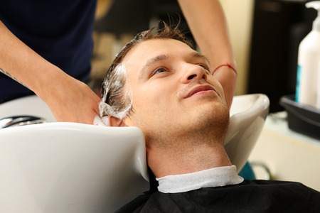 shorten: Female hands washing hair to handsome smiling man at hairdresser with shampoo before haircut. Keratin restoration, latest trend, fresh idea, haircut picking, shorten tips, instrument store concept Stock Photo