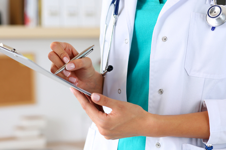 prescription medicine: Female medicine doctor hand holding silver pen writing something on clipboard closeup. Medical care, insurance, prescription, paper work or career concept. Physician ready to examine patient and help