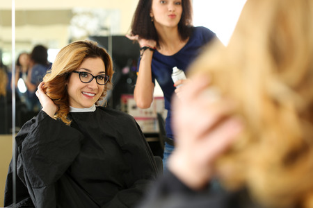 shorten: Beautiful smiling blonde woman at hairdresser checking and fixing new curly hairdo with hand. Keratin restoration, latest trend, fresh idea, haircut picking, shorten tips, instrument store concept Stock Photo
