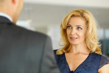 Man en glimlachende rijpe vrouw praten in het kantoor. Opdrachtgever of metgezel ondersteuning, witte kraag partner, winst, positieve vriendelijke top, bediende, koopje of deal discussie begrip