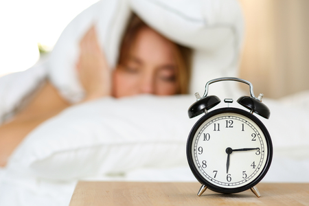 oversleep: Alarm clock standing on bedside table going to ring while woman cover head and ears with pillow making unpleasant face. Early awakening, not getting enough sleep, oversleep, getting work time concept