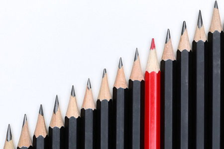 Red pencil standing out from crowd of plenty identical black fellows on white background. Leadership, uniqueness, independence, initiative, strategy, dissent, think different, business success concept