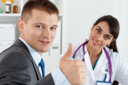 ottimo: Uomo d'affari sorridente in abito che mostra il segno OK o approvazione con pollice fino a ufficio del medico reception. Alto livello di soddisfazione e la terapia di qualità, stile di vita sano fisico, miglior concetto ospedale Archivio Fotografico