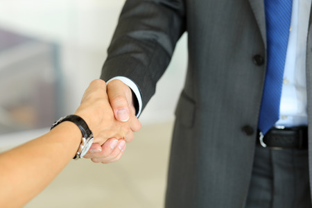 handclasp: Businessman and woman shake hands as hello in office closeup. Friend welcome, introduction, greet or thanks gesture, product advertisement, partnership approval, arm, strike a bargain on deal concept Stock Photo