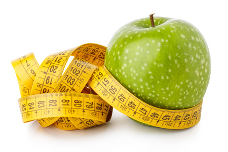 Green ripe apple with measuring tape around it isolated over white background closeup. Fresh tasty breakfast, wellness life style, dietetics or liposuction, great athletic body building concept Stock Photo