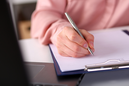 make summary: Female hand holding silver pen closeup. Woman writing letter, list, plan, making notes, doing homework. Student studying. Education, self development and perfection concept