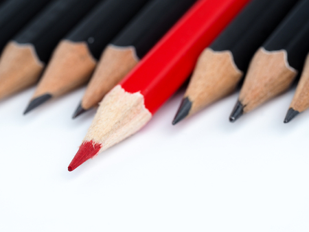 Red pencil standing out from crowd of plenty identical black fellows on white background. Leadership, uniqueness, independence think, initiative, strategy, dissent, business success concept Stock Photo