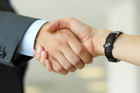 Businessman and woman shake hands as hello in office closeup. Friend welcome, introduction, greet or thanks gesture, product advertisement, partnership approval, arm, strike a bargain on deal concept 版權商用圖片