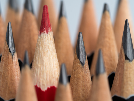 Red pencil standing out from crowd of plenty identical black fellows on grey background. Leadership, uniqueness, independence think, initiative, strategy, dissent, business success concept Stock Photo