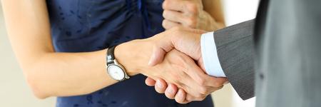Uomo d'affari e donna si stringono la mano come ciao in ufficio primo piano. Amico di benvenuto, introduzione, salutare o gesto grazie, pubblicità del prodotto, l'approvazione di partnership, il braccio, colpire un affare su affare concetto
