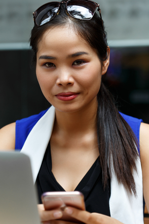 irc: Vietnam smiling student using notebook pc and cell phone outdoor. Young businesswoman in coworking place. White collar worker, effective management, startup ambition, irc, mobile office concept