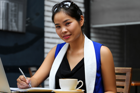 irc: Beautiful vietnam smiling female student with notebook pc outdoor. Young businesswoman in coworking place. White collar worker, effective management, startup ambition, irc, mobile office concept