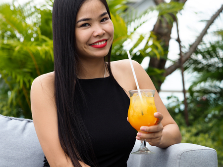 Beautiful young brunette vietnam girl wearing black dress holding tasty fruit cocktail. Evening makeup, red lips, fast date, international relations and acquaintance, nlp, escort service concept