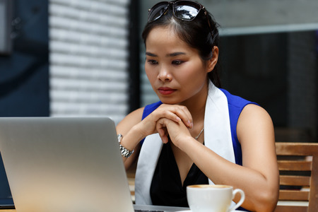 irc: Beautiful vietnam female student using laptop pc outdoor. Young businesswoman look in notebook display, drink coffee. White collar worker, effective management, startup ambition, irc concept