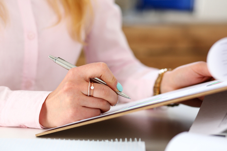 revisando documentos: Female arms hold silver pen and pad with financial statistics at workplace closeup. White collar check money papers, school or college homework exercise, internal Revenue Service inspector concept Foto de archivo
