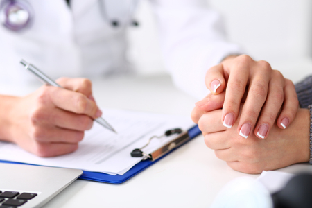 Friendly female doctor hold patient hand in office during reception. Examination result, positive test, calm down, promise and cheer up, grief and suffer, treatment, condolence, ethics, visit concept Stock Photo