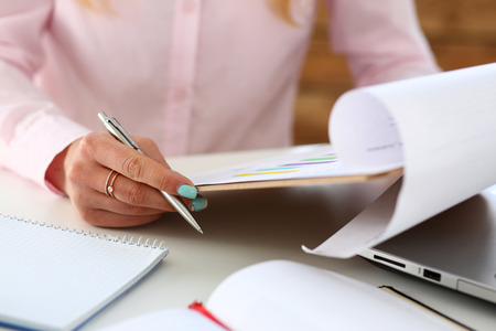 Female hands hold silver pen and pad with financial statistics at workplace closeup. White collar check money papers, stock exchange market, internal Revenue Service inspector, earning list concept