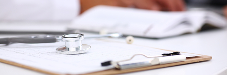 Stethoscope head lying on medical forms closeup while medicine doctor working in background. Patient history list, visit check, 911, medical calculation and statistics, healthy lifestyle concept