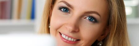 La empresaria sonriente rubia hermosa trabaja con la computadora portátil que mira en retrato de la cámara. Trabajador de cuello blanco en el lugar de trabajo, oferta de trabajo, chat web de internet, telefonía inalámbrica ip, concepto de red social Foto de archivo - 86361880