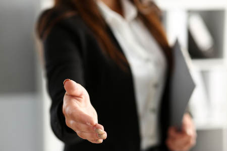 Businesswoman offer hand to shake as hello in office closeup. Serious solution, friendly support service, excellent prospect, introduction or thanks gesture, gratitude, invite to participate concept