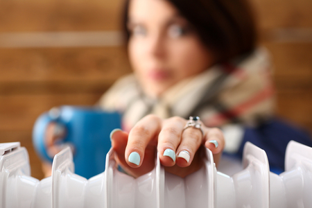 Pensive woman wrapped in cozy scarf hugging mug of hot tea trying to warm up her arm with heater closeup. Domestic power consumption saving mode and energy economy lifestyle, subambient house concept