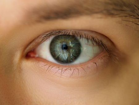 Male left emerald green coloured eye extreme closeup. Oculist and perfect vision, contact lens concept Stock Photo