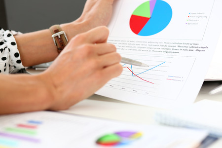 Female arm holding silver pen point in financial graph solving and discussing problem with colleague closeup. Situation examination at board council, sale adviser job, stock exchange market profit Stock Photo