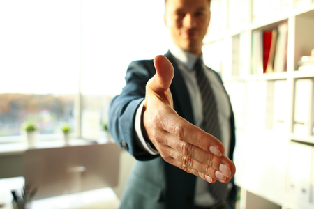 Man in suit and tie give hand as hello Stockfoto