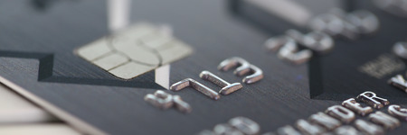 Embossed chipped credit card lying on silver keyboard