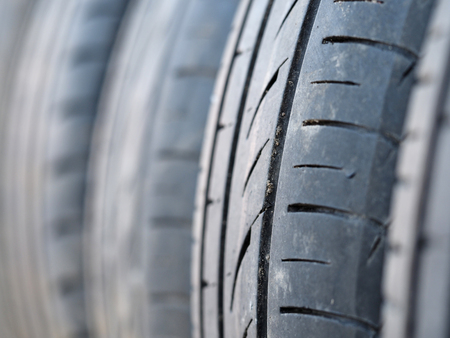 Set of used tyres stand in row at warehouse closeup