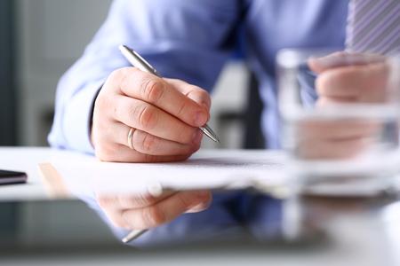Remplir le bras et signer un formulaire important coupé au tampon avec un stylo argenté en gros plan. Faire note geste lire pacte agent de vente banque emploi prêt crédit hypothèque investissement financement chef droit juridique participer à la campagne