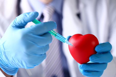Physician arms wearing protective blue gloves stick needle into toy red heart closeup. Cardiologist surgeon idea cardiac supplement for long healthy life concept