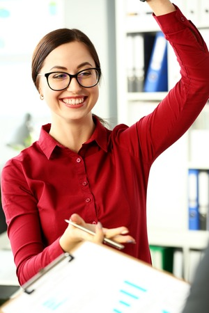 Beautiful smiling clerk wearing glasses with silver pen in arm deliberate on problem at office workplace portrait. Partnership dispute talk client win situation successful visit benefit collaboration Stock Photo