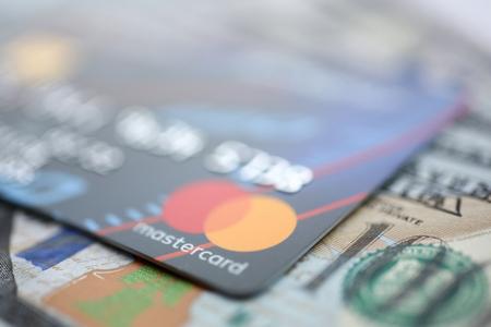 Minsk, Belarus - February 08,2017: Embossed chipped mastercard credit card and hundred dollar bank notes closeup Sajtókép