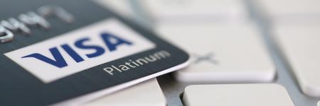 Minsk, Belarus - October 19,2018: Embossed chipped VISA Platinum credit card lying on silver keyboard closeup