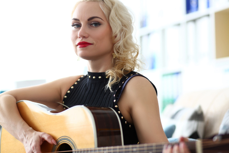 Blond adult guitar teacher playing instrument and looking in camera portrait