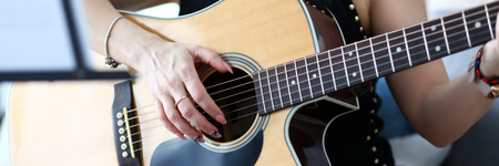 Letterbox of female hands holding western acoustic guitar sitting on couch at home rehearsing some musical phrase closeup Standard-Bild