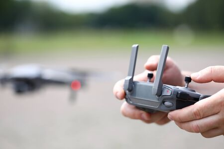 Modern video recording drone controlled with male hands holding remote controller closeup