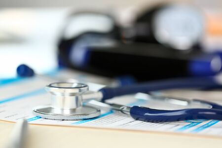Stethoscope head and silver pen lying on medical application form at worktable in doctor office closeup