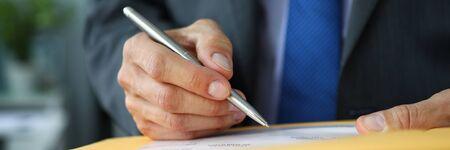 Vue de la boîte aux lettres d'un employé masculin en costume-cravate sur le lieu de travail tenir dans les mains un stylo argenté remplissant un modèle de formulaire de demande pour envoyer une lettre de voeux quelque part en gros plan. Banque d'images
