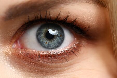 Close-up view of pretty amazing female left eye with happy and excited facial expression