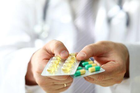 GP in der Klinik, die Packung mit verschiedenen Blisterpackungen in Nahaufnahme hält. Verschreibungspraxis für lebensrettende Medikamente und legales Drogeriekonzept Standard-Bild