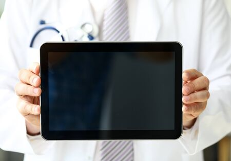 Male GP holding mobile computer pc demonstrating something to patient close-up